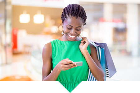 Retail Industry | Everlytic | Email and SMS Marketing | Young black woman in green dress on phone while shopping picture