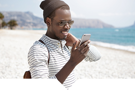 Travel Industry | Everlytic | Email and SMS Marketing | Young black man on phone on the beach | jpeg