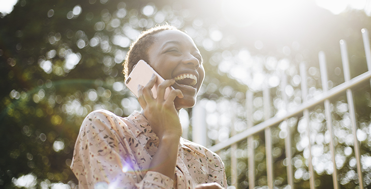 10 Reasons Why You Should Use Voice Broadcasting | Everlytic | Digital Communication Software | Email Marketing | Woman laughing on the phone | African woman on phone | Black woman on phone