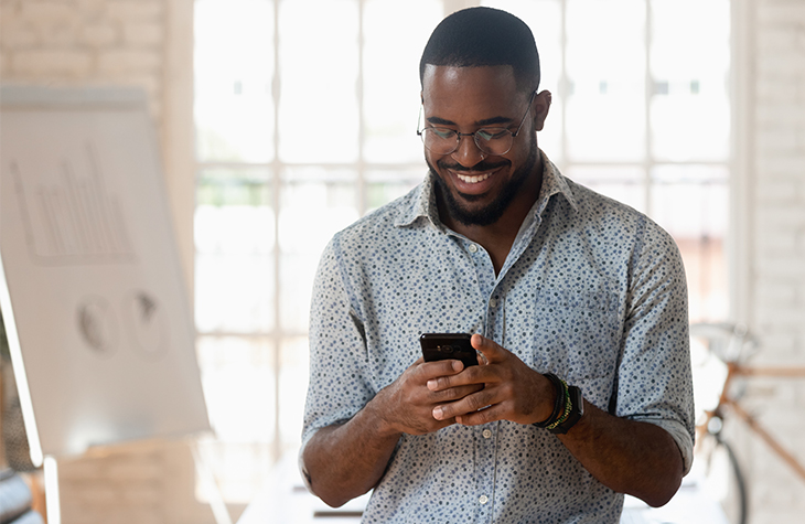 How & Why to Communicate During COVID-19   Marketing   Blog   Everlytic   Happy man looking at phone